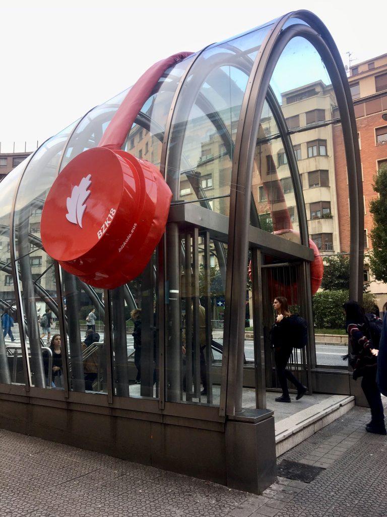 Publicidad exterior creativa que muestra unos auriculares rojos sobre una boca de metro en Bilbao
